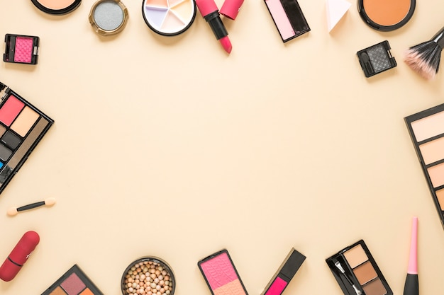 ベージュのテーブルに散在しているさまざまな化粧品の種類