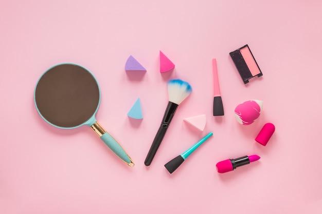 テーブルの上のさまざまな化粧品とミラーします。