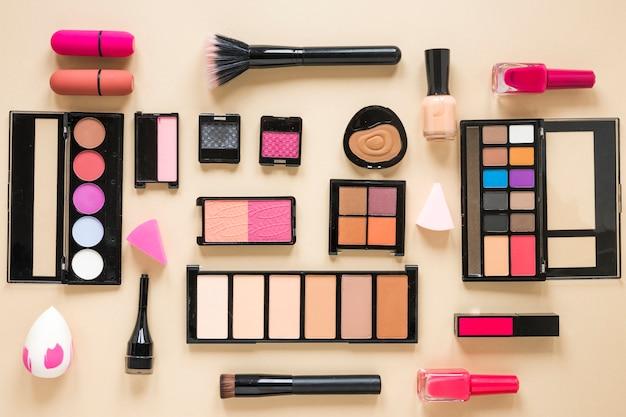 Различные виды косметики разбросаны по бежевому столу