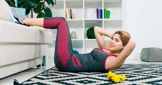 柔軟な金髪の若い女性が彼女の足を自宅でストレッチ