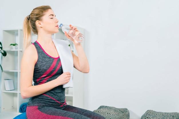 スポーツウェアのボトルからの水を飲むのフィットネス若い女性