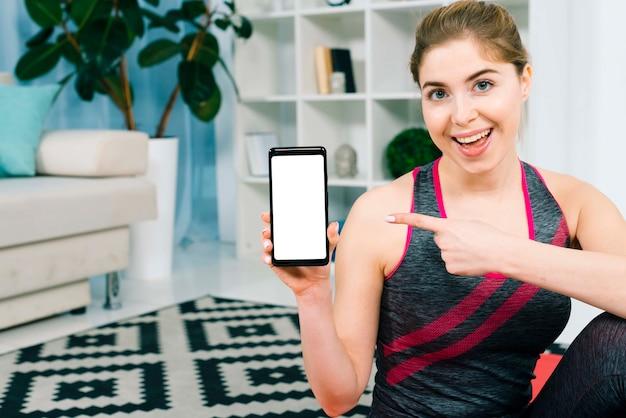 リビングルームに座っている彼女の携帯電話に向かって彼女の指を指している若い女性の笑みを浮かべてください。