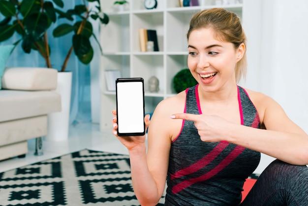 白い表示画面を持つ彼女のスマートフォンを示すフィット若い女性