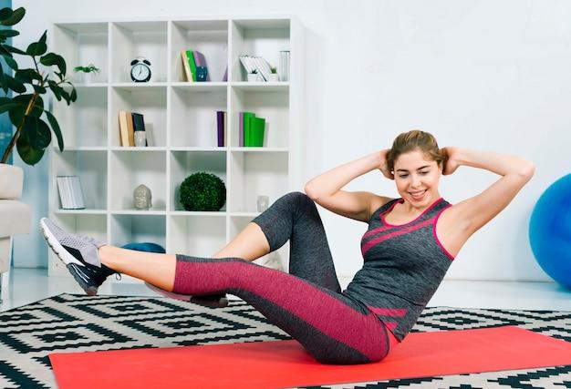 リラックスした運動をしている赤い運動マットの上に座っている若い女性の笑みを浮かべてください。