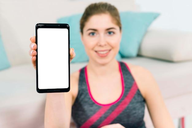 Расфокусированным молодая женщина сидит возле дивана, показывая смартфон с пустой белый экран