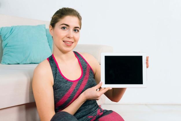 空白のデジタルタブレットを示す笑顔の若い女性の肖像画
