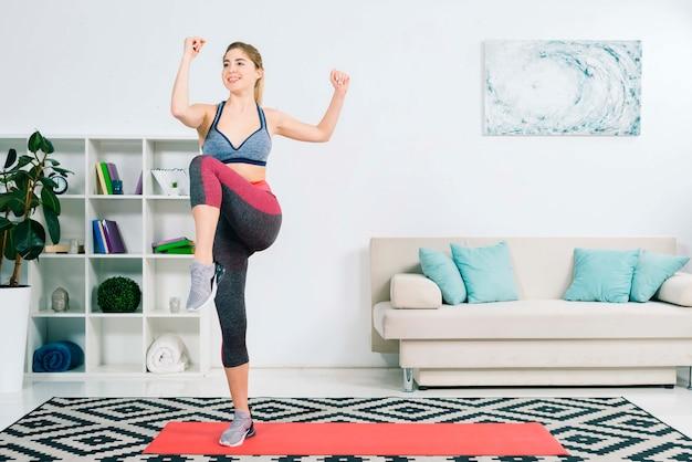 Стройная женщина в спортивной одежде делает упражнения в гостиной