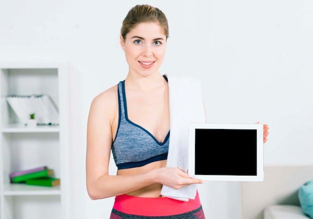 デジタルタブレットを示す肩越しにタオルでスポーツウエアで笑顔の若い女性の肖像画