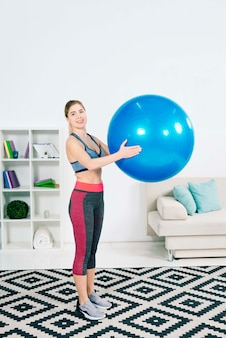 青いピラティスボールを保持しているリビングルームに立っているスリムフィット若い女性