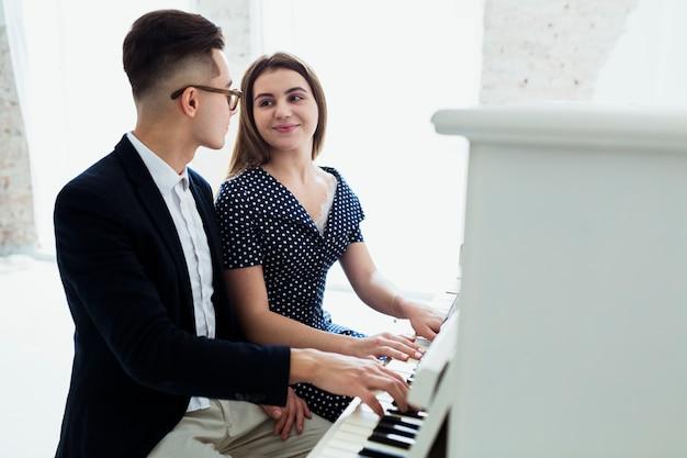 お互いを見てピアノを弾く魅力的な若いカップル