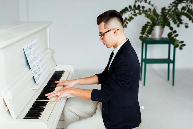グランドピアノを弾く若い男の側面図