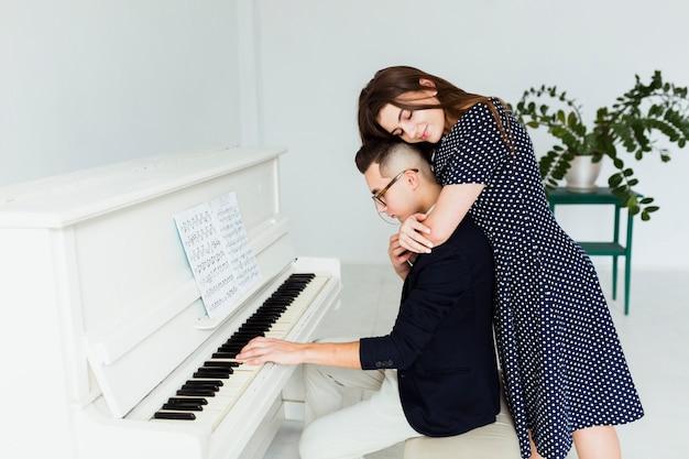 ピアノを弾く後ろから彼女のボーイフレンドを抱きしめる若い女性