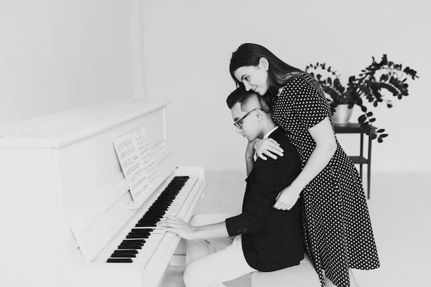 自宅でピアノを弾く彼女のボーイフレンドを抱きしめる笑顔の若い女性