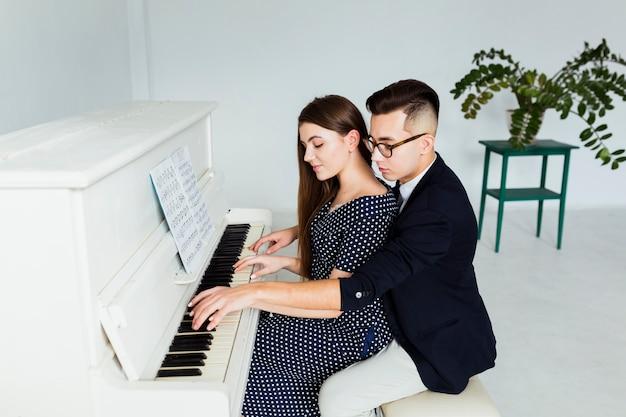 ピアノを弾く彼女のガールフレンドを教えるハンサムな若い男