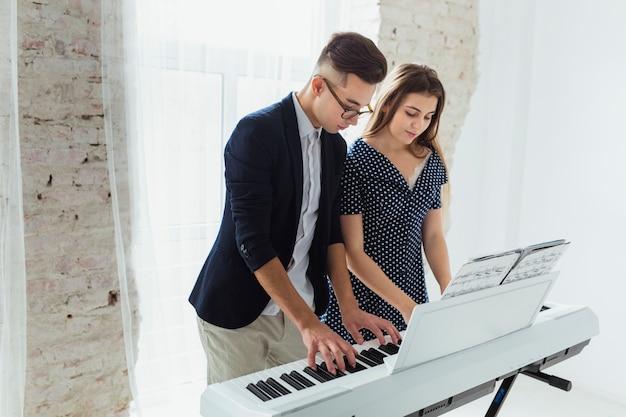 ピアノを弾く白いカーテンの近くに立っている若いカップル