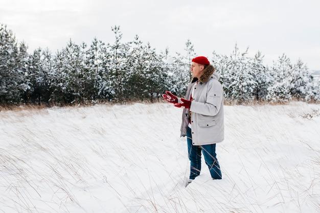 冬の森の暖かいジャケット立っている男
