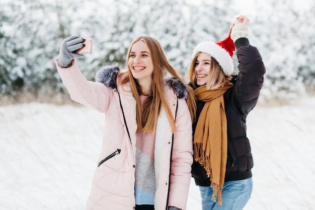 Женщины в шляпу санта принимая селфи в зимнем лесу