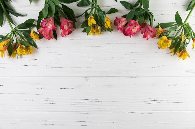 白い木製の織り目加工の背景にアルストロメリアの花の花束