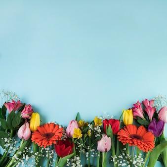 テキストを書くためのコピースペースと青い表面に色とりどりの花