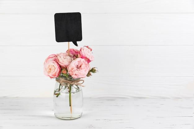 白い木製の背景にバラのガラス瓶の中の黒い吹き出し支柱