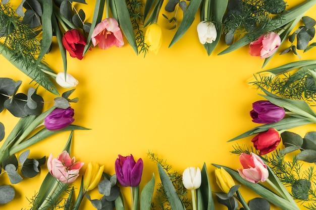 黄色の表面の背景に色とりどりのチューリップフレームの俯瞰
