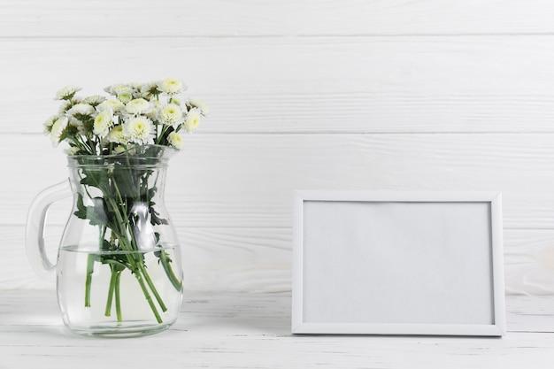 木製の背景の空白の枠に対してガラスの水差しの菊の花