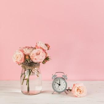 ピンクの背景に対して木製の机の上の目覚まし時計の近くのバラの花瓶