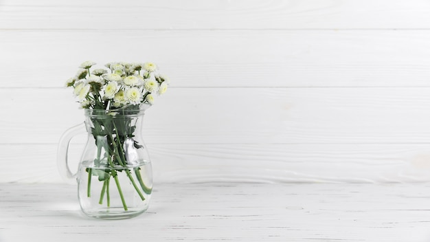白い木製の背景に対してガラスの水差しの中の菊の花