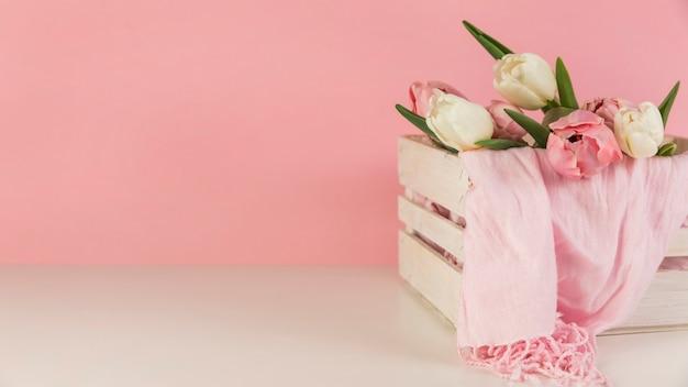 美しいチューリップとピンクの背景の白い机の上の木箱でスカーフ