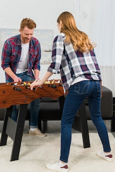 自宅でテーブルサッカーの試合を楽しんでいるカップルの背面図