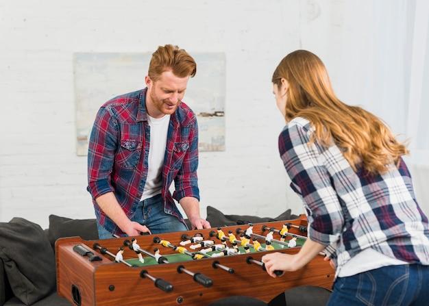 Молодые сосредоточены пара весело с игрой в настольный футбол