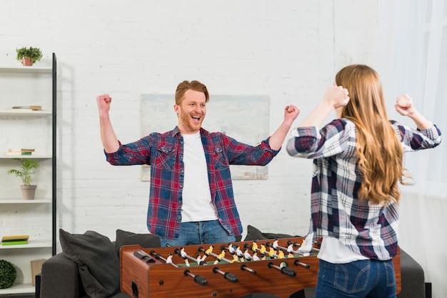 Крупный план молодая пара празднует победу после игры в настольный футбол