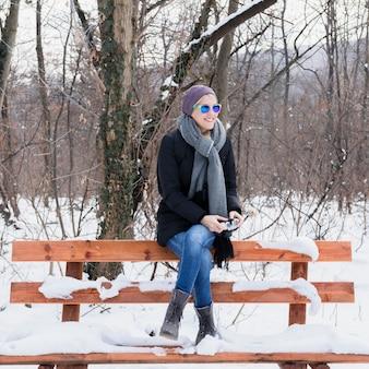 雪でベンチに座っている美しい若い女性