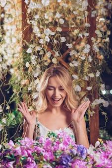 美しい花の花束を見てツタの前に立っている興奮している若い女性