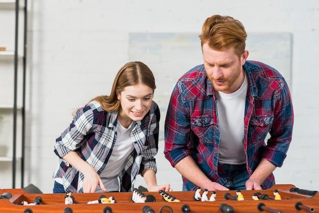 Улыбающиеся молодые пары играют в крытый футбол дома