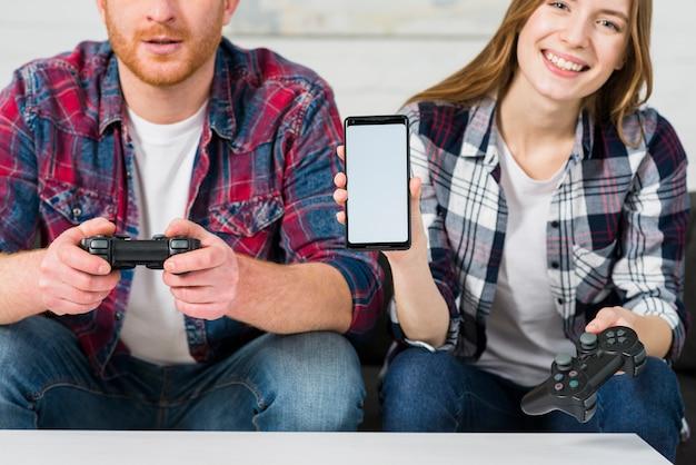 Улыбающаяся девушка сидит со своим парнем, играя в видеоигру, показывая экран мобильного телефона