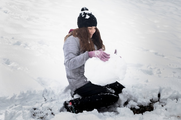 冬の風景の中で雪玉を作る遊び心のある女の子のクローズアップ