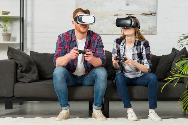 仮想現実を身に着けている若いカップルはリビングルームでビデオゲームをプレイゴーグルします。