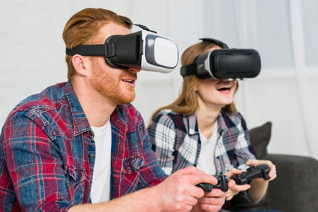 現実を身に着けている笑顔の若いカップルがビデオゲームを楽しんでゴーグルします。