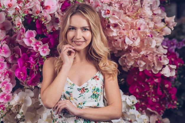 蘭の花の前にあごに立って手を持つ幸せな美しい金髪の若い女性