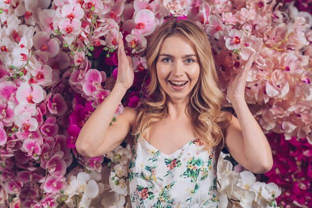 美しい花の蘭の花の前に立っている興奮している若い女性