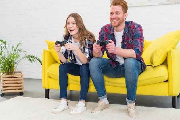 美しいカップルが楽しんでコンソールでビデオゲームをプレイ