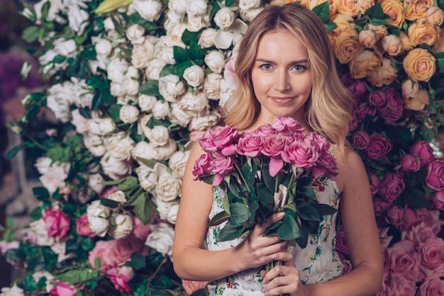 花の背景に対してピンクのバラの花束を保持している若い女性の肖像画
