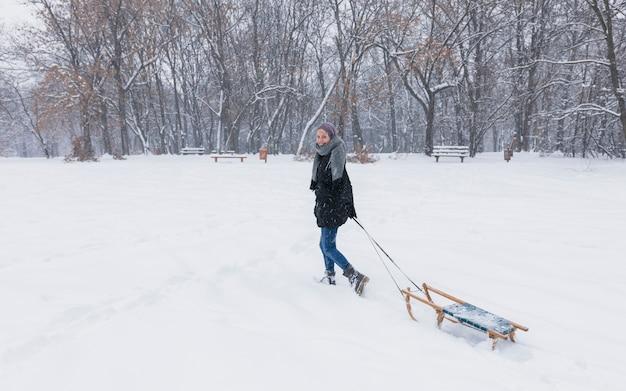 森で雪の風景に空の木製そりを引く若い女性