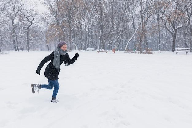 冬の雪に覆われた土地を走る暖かい服を着ている女性