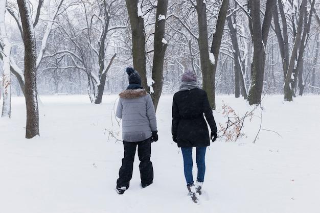冬の日に森を歩く彼女の娘を持つ背面母