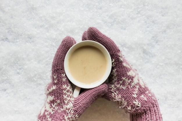雪に覆われた土地にコーヒーカップを保持している居心地の良い手袋で人の手