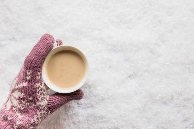 雪に覆われた土地の上に一杯のコーヒーを持っている人間の手