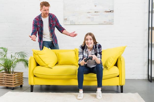 黄色のソファをすくめて後ろに立っている彼女のボーイフレンドと一緒にビデオゲームをプレイ若い女性