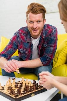彼女のガールフレンドとチェスをする笑みを浮かべて若い男の肖像